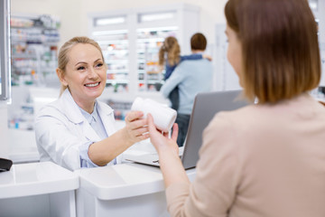 Help customer. Glad female pharmacist assisting woman and grinning