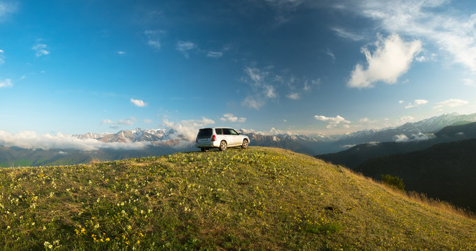 car stands on a mountain meadow with flowers and grass against the backdrop of the top of the mountain ranges snow-capped in the clouds