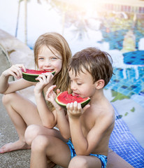 Summer vacation - children eat watermelon by the pool