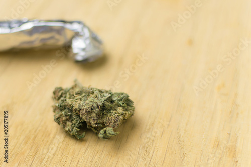 The use of marijuana. Homemade device for smoking marijuana and a bud of marijuana on a wooden background.