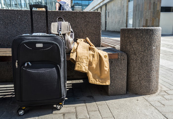 Large black wheeled suitcase standing on the floor in airport, a woman's backpack and cloak on the bench