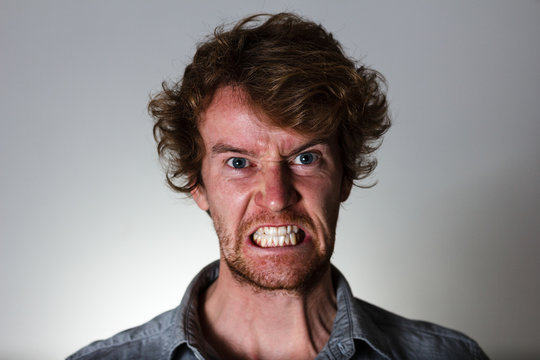 Angry young man with clenched teeth