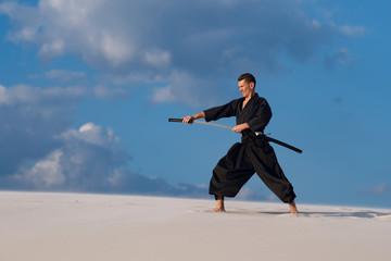 Man training Japanese martial arts in desert