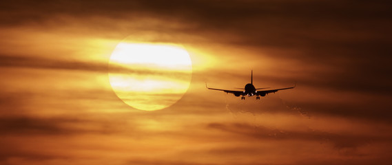 Beautiful sunset with airplane landing