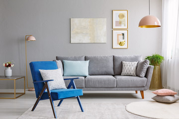 Blue armchair near grey settee in modern living room interior with poster and pink lamp. Real photo