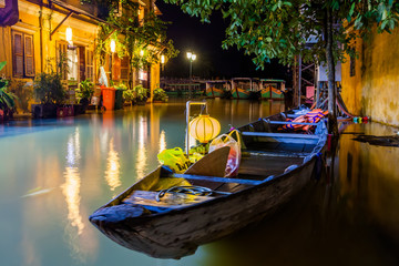 Hoi An, Vietnam. Street view with traditional boats on a background of ancient town