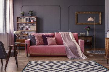 Pink velvet lounge with cushions and blanket standing in the middle of dark grey living room interior with molding on the wall, geometric carpet and two metal lamps