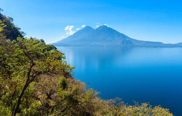 View from Lake Atitlan in the early morning, blue skys and clear water, beautiful magic lake with volcanos and indigenous people in the highland of Guatemala