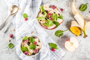 Healthy summer breakfast, fruit and berry salad with spinach, granola, apple and banana, white marble background  above