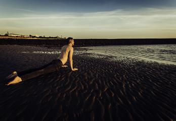 Joven haciendo yoga en la arena de las playas de Sanlúcar de Barrameda