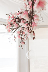 Photo of original wedding floral decoration hanging on the ceiling with big window on background