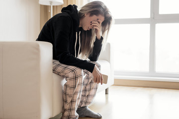Depressed woman sitting in couch with mobile phone in hand