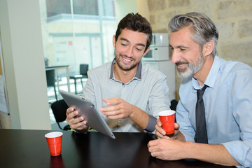Men drinking coffee and looking at tablet