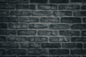 Dark gray brick wall close-up texture - rough brickwork background