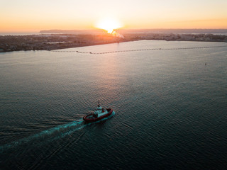 Aerial photo of a small tugboat at sunset