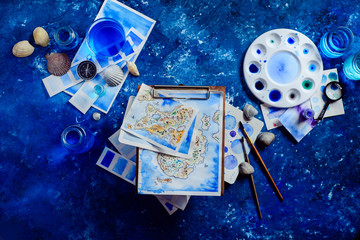 Artist workplace with a watercolor map, sketches, seashells and compass on a navy blue background with copy space. Travel flat lay header.