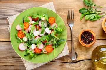 Vegetarian salad of arugula, tomato, radish and mozzarella cheese on an old wooden table.