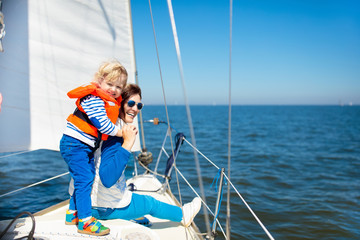 Family sailing. Mother and child on sea sail yacht.