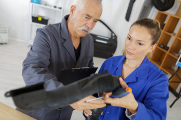 young female mechanic with teacher