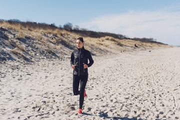 Fit athletic woman jogging along a sandy beach