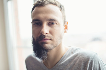 Handsome man half beard standing in front of white background with half of his face with scruffy beard, the other half has a beautiful trimmed beards and smart look hair style