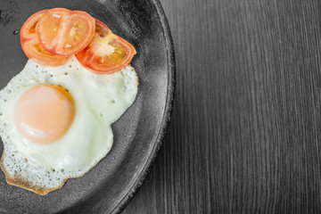 fried egg with tomatoes in a cast-iron frying pan on a wooden table
