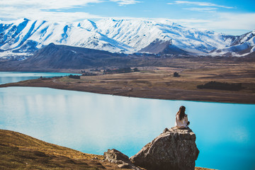 A girl with long hair sit on a rock in Mt. John looking at Lake Tekapo