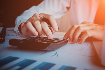 Asian business man analyze and discuss the situation on the marketing data online and calculate about cost in the meeting room. Business finances and accounting
