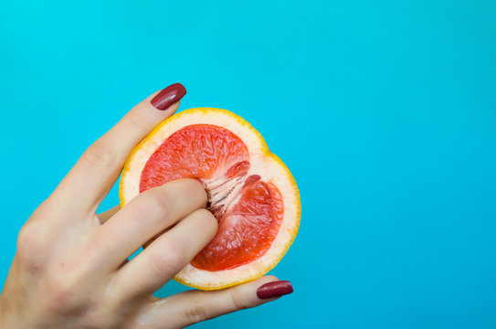 Two fingers on grapefruit on blue background. Sex concept.