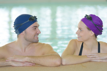 young couple of swimmers inside swimming pool