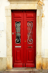 Red door of a house in Faro, Algarve, South of Portugal