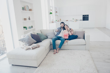 Full size portrait of stylish positive couple sitting in modern white apartment using console looking comedy funny channel program film on television hugging embracing eating snack