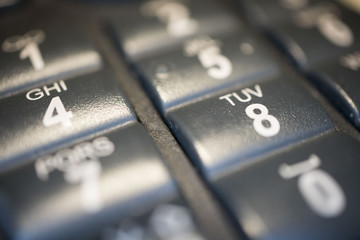 Modern black business landline telephone keypad buttons close-up.