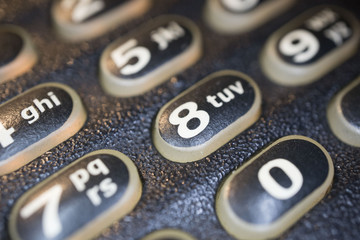 Modern black business landline telephone keypad buttons close-up.