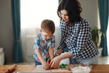 Mother and son dressed in plaid shirts are cooked in the kitchen of flour and dough