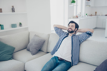 Portrait of positive cheerful single man with stubble in jeans shirt sitting on sofa in livingroom holding hands behind the head with close eyes enjoying recreation