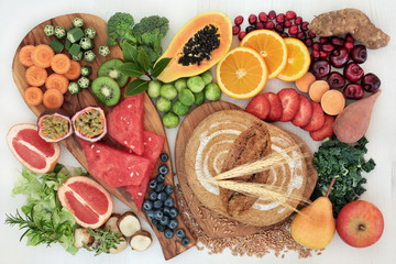 High dietary fibre super food concept with fresh fruit, vegetables, whole grain rye bread, herbs and spices top view on rustic background. Foods high in antioxidants, anthocyanins and vitamins.