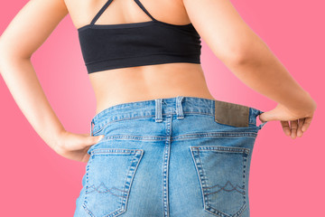 Close up portrait of young woman showing successful weight loss with her jeans on isolate background, Healthcare, Diet concept