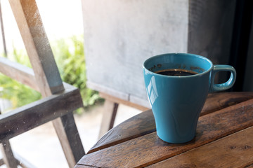 Closeup image of a blue mug of hot coffee on vintage wooden table in cafe