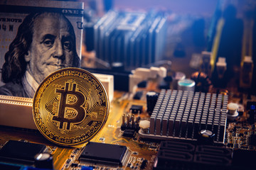Golden bitcoin cryptocurrency on computer electronic circuit board