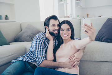 Portrait of lovely positive couple sitting on the floor indoor in house using smart phone shooting self portrait on front camera having video-call fun, enjoying time together
