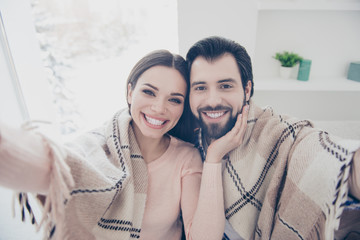 Self portrait of cheerful toothy couple covered with blanket shooting self portrait on front camera woman holding hand on face of lover
