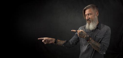 Portrait eines bärtigen tätowierten Mannes, vor schwarzem Hintergrund