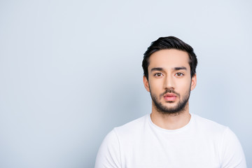 Portrait with copy space empty place of attractive strict guy with bristle black hair in white outfit looking at camera isolated on grey background