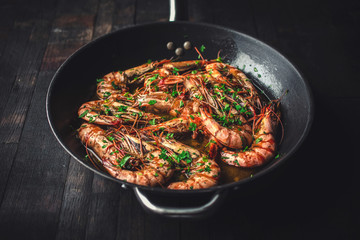 Shrimps fried in a pan. Classic recipe - parsley, garlic, chilli peppers and white wine.