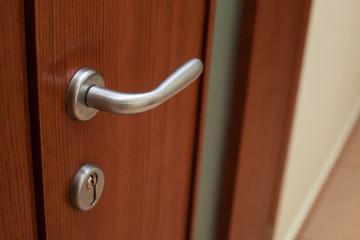 Silvery door handle and lock on the brown wooden door