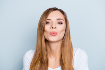 Portrait of lovely cute brown-haired girl sending kiss with pout lips isolated on grey background looking at camera