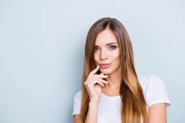 Portrait of cute trendy girl holding fingers on chin with dreamy seducing expression isolated on grey background looking at camera