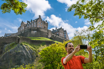 A happy young man tourist at Edinburgh Castle taking selfie on mobile phone.