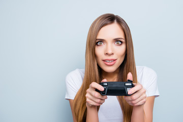 Portrait with copy space empty place of funny playful girl holding joystick in hands she is video game lover playing with spectacular expression isolated on grey background